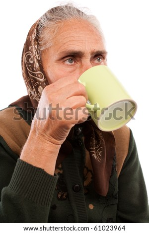 Closeup portrait of an old woman drinking from a cup - stock photo