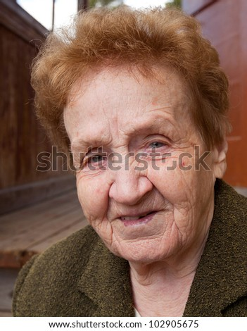 Closeup portrait of an senior woman 85 years old, looking at camera. - stock photo
