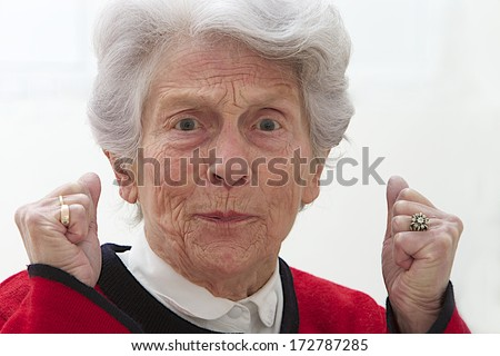 Closeup portrait of angry, furious elderly woman raising clenched hand - stock photo