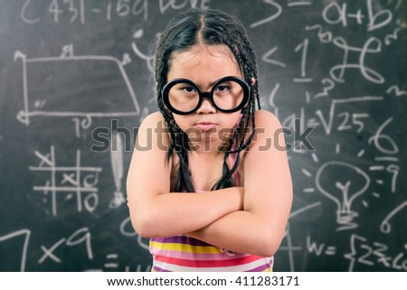 Closeup portrait of angry girl ,with a blackboard in the background - stock photo