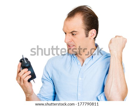 Closeup portrait of angry, mad, demanding boss, business man, funny looking guy holding alarm clock, screaming, hates time passing by so quickly pushing project deadline, isolated on white background - stock photo