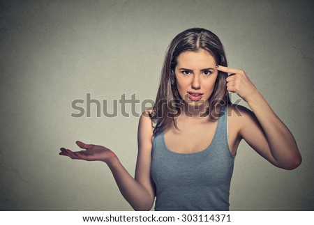 Closeup portrait of angry mad young woman gesturing with her finger against temple asking are you crazy? Isolated on gray wall background. Negative emotions facial expression feeling body language  - stock photo