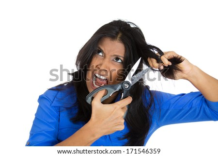 Closeup portrait of angry pissed off pretty woman having bad day about to chop off her black hair with scissors, isolated on white background. Negative emotion facial expression feelings, attitudes