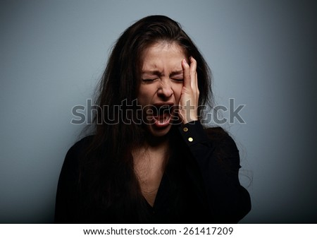 Closeup portrait of angry, sad and desperate shouting woman on dark background - stock photo