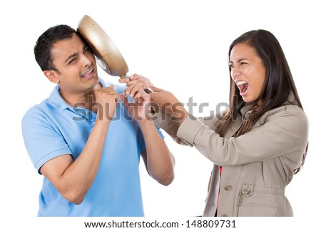 Closeup portrait of angry young woman hitting surprised shocked funny man on face with frying pan, isolated on white background. Negative emotion facial expression feelings, reaction, situation. - stock photo