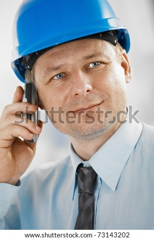 Closeup portrait of architect wearing hardhat, talking on mobile, looking at camera.? - stock photo
