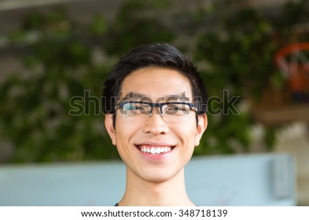 Closeup portrait of asian positive cheerful young man in glasses - stock photo