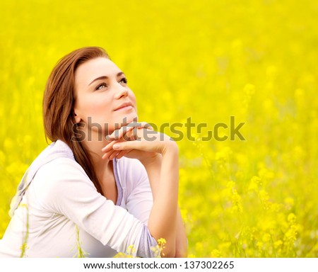 Closeup portrait of attractive brunette female sitting down on yellow floral field, rapeseed plantation, summer vacation concept - stock photo