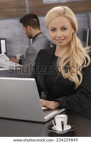 Closeup portrait of attractive businesswoman sitting at desk, working with laptop computer, smiling, looking at camera. - stock photo