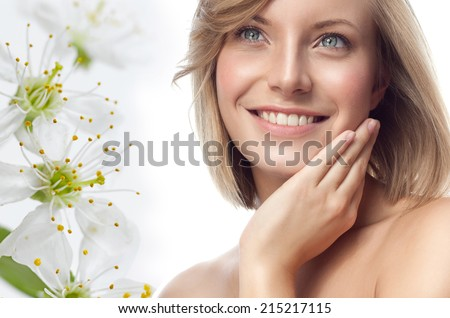 closeup portrait of attractive  caucasian smiling woman blond isolated on white studio shot lips toothy smile face hair head and shoulders looking up blue eyes tooth flowers spring aroma - stock photo