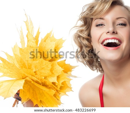 closeup portrait of attractive  caucasian smiling woman blond isolated on white studio shot lips toothy smile face hair  looking at camera blue eyes tooth hand holding yellow marple autumn leaves