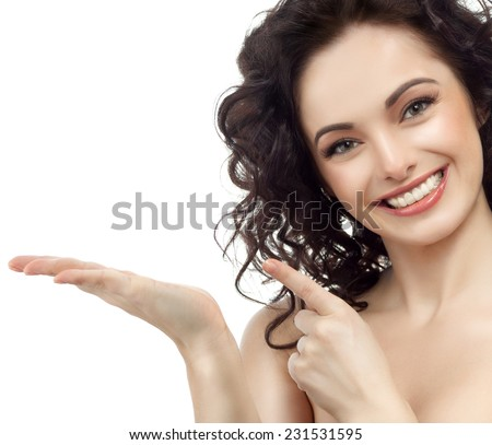 closeup portrait of attractive  caucasian smiling woman brunette isolated on white studio shot lips toothy smile face hair head and shoulders looking at camera tooth pointing to - stock photo