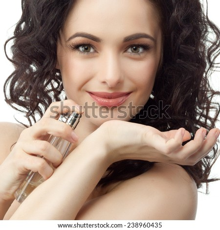 closeup portrait of attractive  caucasian smiling woman brunette isolated on white studio shot lips face hair head and shoulders looking at camera applying perfume - stock photo