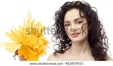 closeup portrait of attractive  caucasian smiling woman brunette isolated on white studio shot lips  face hair head and shoulders looking at camera hand holding yellow marple autumn leaves