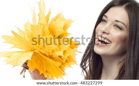 closeup portrait of attractive  caucasian smiling woman brunette isolated on white studio shot lips toothy smile face hair head and shoulders tooth hand holding yellow marple autumn leaves