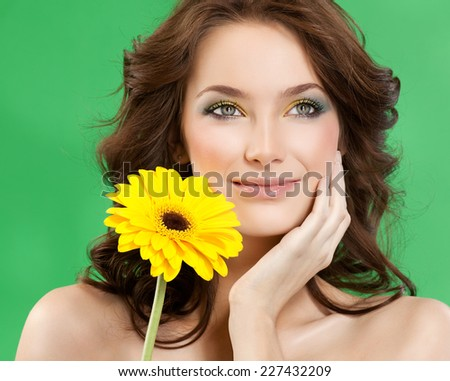 closeup portrait of attractive  caucasian smiling woman brunette studio shot lips  face hair head and shoulders hands skin makeup yellow flower - stock photo