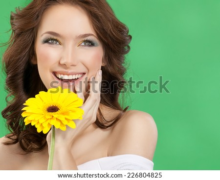 closeup portrait of attractive  caucasian smiling woman brunette studio shot lips toothy smile face hair head and shoulders  tooth skin makeup yellow flower - stock photo