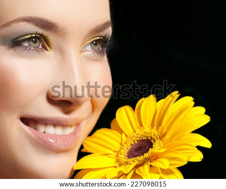 closeup portrait of attractive  caucasian smiling woman  studio shot lips toothy smile face closeup skin makeup head  tooth eyes flower yellow - stock photo