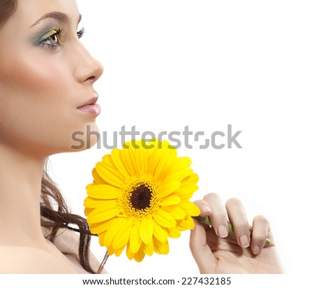 closeup portrait of attractive  caucasian  woman brunette isolated on white studio shot lips face skin makeup hair head and shoulders yellow flower - stock photo