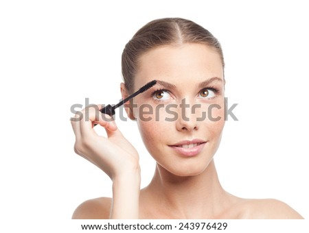 closeup portrait of attractive  caucasian woman brunette isolated on white studio shot lips  face head and shoulders looking up applying mascara eyes makeup - stock photo