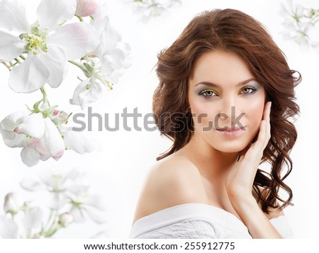 closeup portrait of attractive  caucasian  woman brunette isolated on white studio shot lips  face hair head and shoulders looking at camera skin makeup spring flowers - stock photo