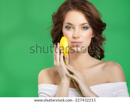 closeup portrait of attractive  caucasian  woman brunette  studio shot lips  face hair head and shoulders looking at camera skin makeup yellow flower aroma spring summer - stock photo