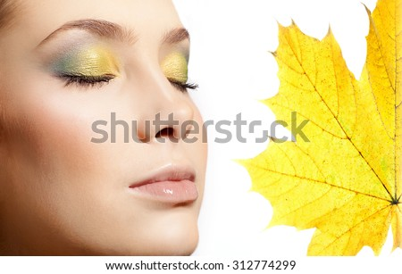closeup portrait of attractive  caucasian  woman  isolated on white studio shot lips  face closeup makeup  head eyes closed skin yellow maple leaf autumn - stock photo