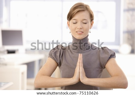Closeup portrait of attractive female office worker, meditating with closed eyes.? - stock photo