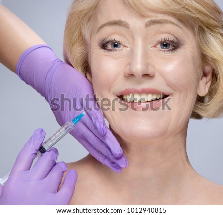 closeup portrait of attractive old mature caucasian woman blond  on blue background studio shot lips face  head and shoulders skin care hands gloves lifting plastic