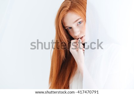 Closeup portrait of attractive redhead woman lookin at camera