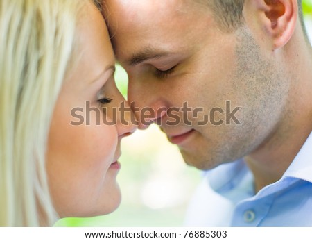 Closeup portrait of attractive romantic couple outdoors. - stock photo