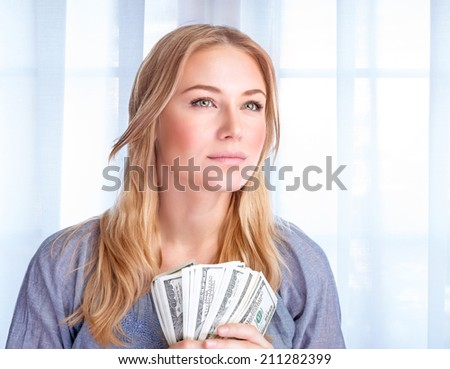 Closeup portrait of attractive serious young business woman holding in hands american dollars, winning financial lottery, success concept - stock photo