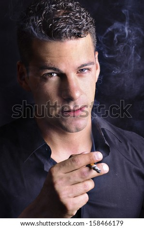Closeup portrait of attractive smoker in low key with side light.  - stock photo