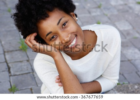 Closeup portrait of attractive young african american woman sitting outdoors - stock photo