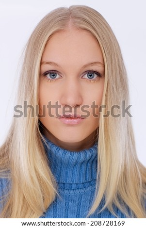 Closeup portrait of attractive young blonde woman with blue eyes, looking at camera. - stock photo
