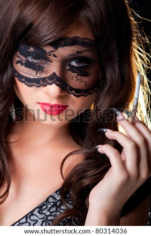 Closeup portrait of attractive young brunette girl with long dark ringlets and fine art manicure wearing lacy mask on her eyes holding graceful silver mouthpiece on black background - stock photo