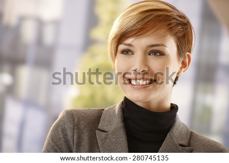 Closeup portrait of attractive young businesswoman in spring sunshine, smiling - stock photo