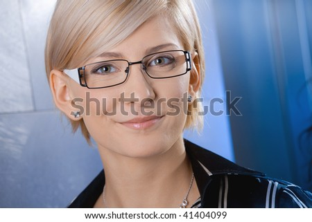 Closeup portrait of attractive young businesswoman wearing glasses, smiling.