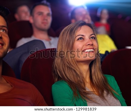 Closeup portrait of attractive young woman in cinema, watching movie, smiling. - stock photo