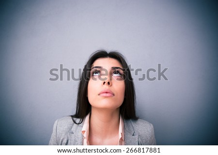 Closeup portrait of attractive young woman looking up at copyspace over gray backound - stock photo