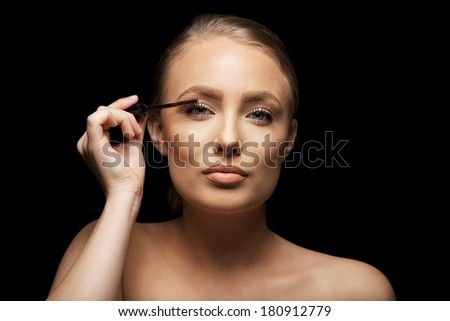 Closeup portrait of attractive young woman putting some mascara onto her eyelashes with make up brush. Beautiful caucasian female model against black background. - stock photo