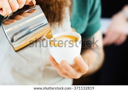 Closeup portrait of barista pouring milk into cup of coffee at the coffee shop - stock photo