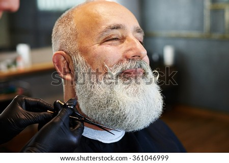 closeup portrait of bearded smiley man in barber shop. barber cutting beard with scissors