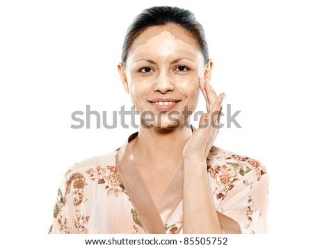 Closeup portrait of beautiful Asian woman applying facial mask in studio isolated on white background - stock photo