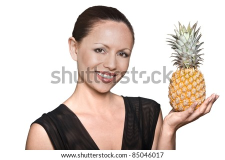 Closeup portrait of beautiful Asian woman holding pineapple in studio isolated on white background - stock photo