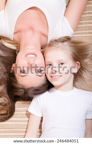 Closeup portrait of beautiful attractive mother and little daughter lying face to face on the sofa - stock photo