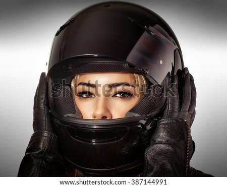 Closeup portrait of beautiful biker woman over gray background, sexy female with glamorous makeup wearing stylish black protective sportive helmet and leather gloves - stock photo