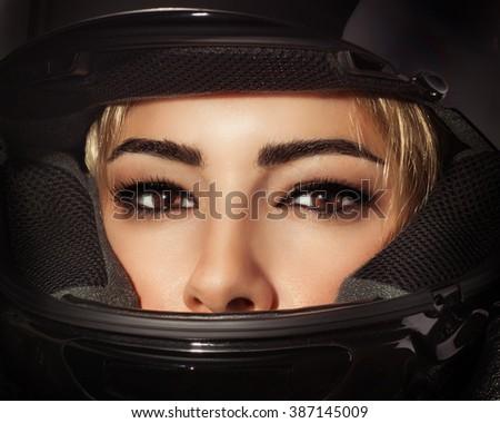 Closeup portrait of beautiful biker woman, sexy female with glamorous makeup wearing stylish black motorbike helmet - stock photo