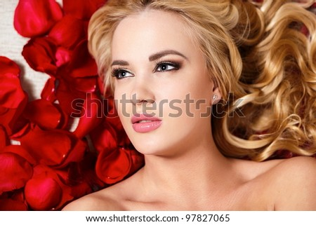 closeup portrait of beautiful blond dreaming girl with red roses long curly hair and bright makeup - stock photo