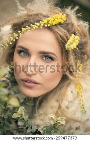 closeup portrait of beautiful blond greeneyed woman with flowers in her hair - stock photo